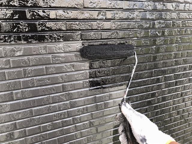 グレーのサイディングに黒の塗料をローラーで塗布
