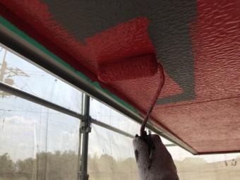 クロっぽい軒天に赤の塗料をローラーで塗布