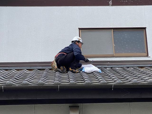 既存の葺き止め漆喰を剥がす作業をしている職人